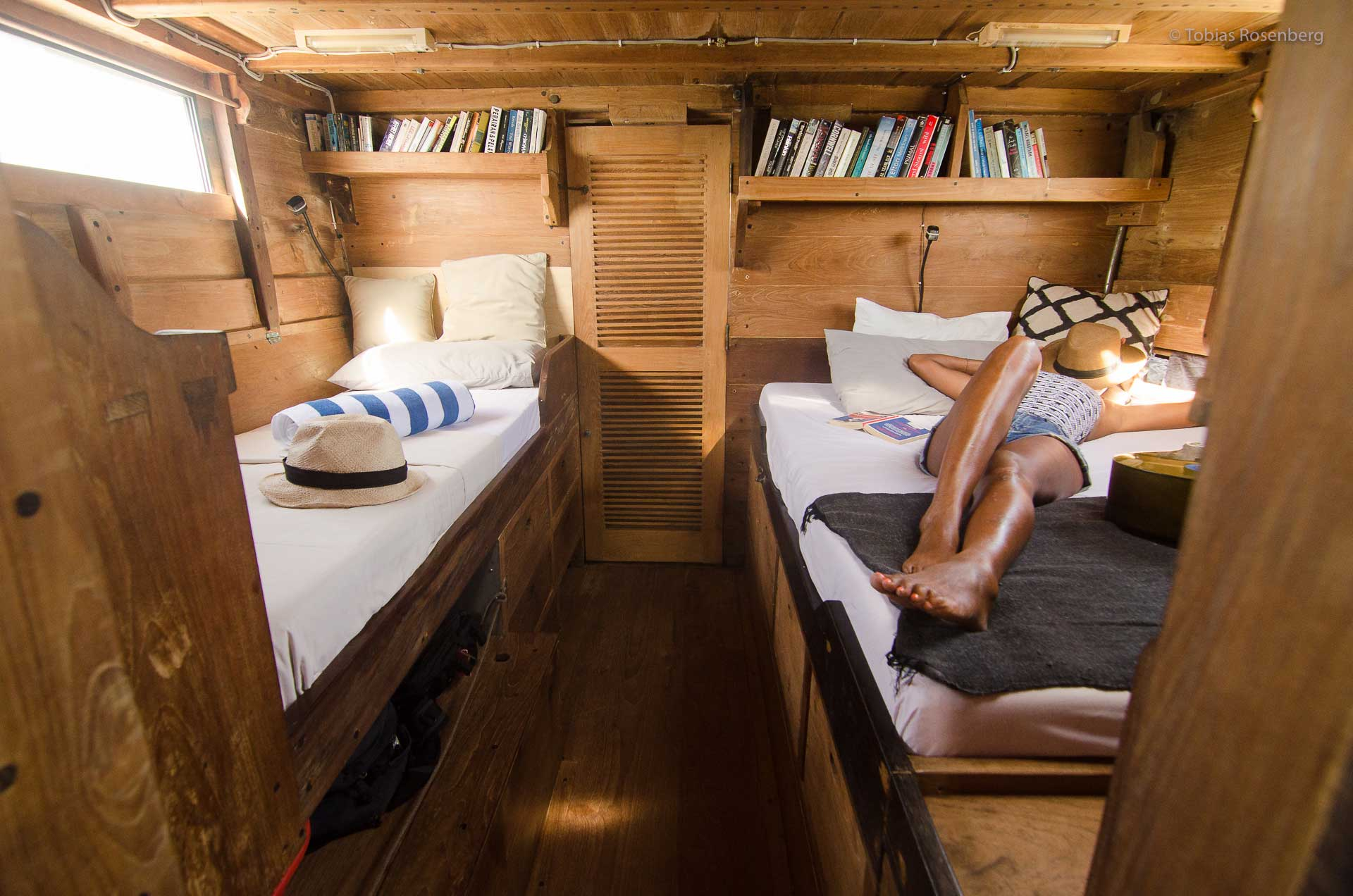 A surfer chilling in boat cabin. Eat, sleep, surf aboard Sri Noa Noa, cozy teak wood cabins and new matrasses! Indo Surf Charter, Sumba Surf Charter, Sumba Surf, Indo Surf Charter, Lombok Surf Charter, Sumbawa Surf Charter, Surf Charter in Indonesia, Surf Boat in Indonesia, Surf in Sumba, Surf in Rote, Surf Charter Indo