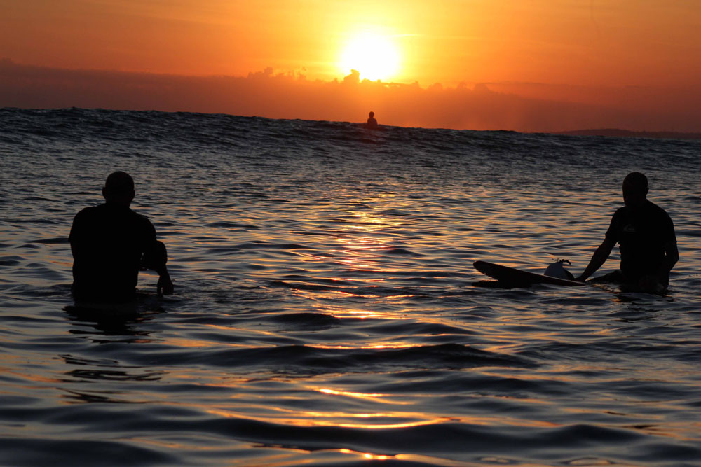 Surfers waiting for waves, surfing another glorious sunset in Sumba
